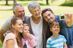 Famille se photographiant avec l'appareil photo numérique en parc Photos stock