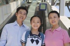 Famille se tenant à côté de l'escalator près de la station de métro Photos libres de droits