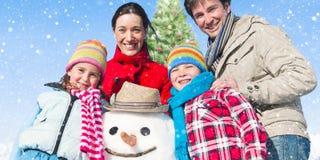 Famille se tenant autour du bonhomme de neige et d'un concept d'arbre de Noël Photos stock