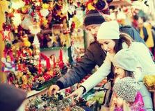 Famille se tenant aux souvenirs coniféres contre Photos stock
