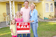 Famille se tenant prêt pour le signe de vente en dehors de la maison photographie stock