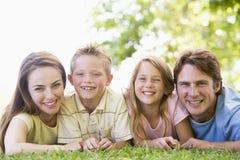 Famille se trouvant à l'extérieur souriant Photo stock