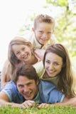 Famille se trouvant à l'extérieur souriant Image stock