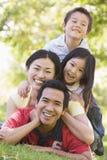 Famille se trouvant à l'extérieur souriant Photographie stock