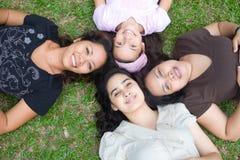 Famille se trouvant sur l'herbe en stationnement extérieur Image stock