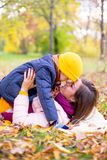 Famille se trouvant sur le parc d'automne de feuilles Photos stock