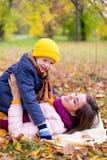 Famille se trouvant sur le parc d'automne de feuilles Image stock