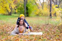Famille se trouvant sur le parc d'automne de feuilles Image libre de droits