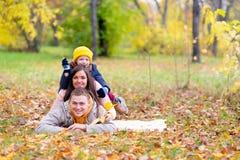 Famille se trouvant sur le parc d'automne de feuilles Photographie stock