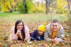 Famille se trouvant sur le parc d'automne de feuilles Photo libre de droits