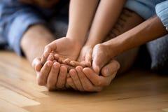 Famille se trouvant sur le plancher tenant ensemble des mains photo libre de droits