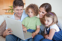 Famille sereine utilisant un ordinateur portable Photographie stock libre de droits