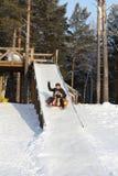 Famille sledding en bas de la côte Photo libre de droits