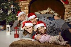 Famille sous l'arbre de Noël dans la cheminée Photos stock