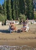 Famille sur des présidences de paquet à la plage 2 de sable Image stock