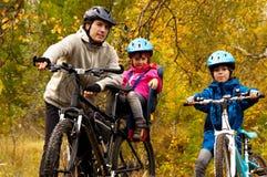 Famille sur des vélos en parc d'automne Photographie stock