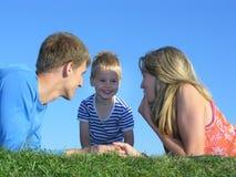 Famille sur des visages d'herbe Photographie stock libre de droits