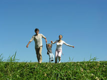 Famille sur l'herbe sous le ciel bleu images stock
