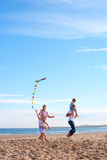 Famille sur la plage avec le cerf-volant Images stock