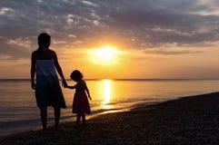 Famille sur la plage de coucher du soleil Photos libres de droits