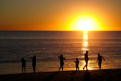Famille sur la plage silhouettée par le coucher de soleil Images stock