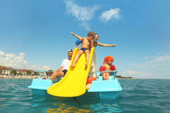 Famille sur le bateau de pédale avec la glissière jaune en mer Photos stock