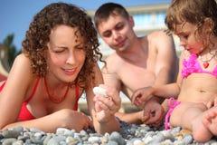 Famille sur le caillou dans les vêtements de bain photographie stock libre de droits