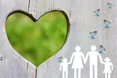 Famille sur le fond en bois avec le coeur vert et les papillons bleus Photographie stock libre de droits