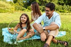 Famille sur le pique-nique Jeune famille heureuse ayant l'amusement en nature Photos libres de droits