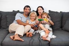 Famille sur le sofa jouant des jeux vidéo Photographie stock libre de droits
