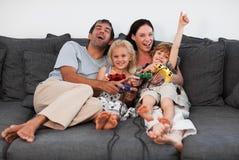 Famille sur le sofa jouant des jeux vidéo Photos libres de droits