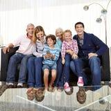 Famille sur le sofa observant Smart TV Image stock