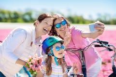 Famille sur le vélo dans des domaines de fleur de tulipe, Hollande images stock
