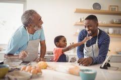 Famille sur plusieurs générations avec de la farine sur le nez se tenant dans la cuisine images stock