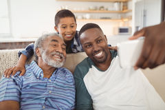 Famille sur plusieurs générations de sourire prenant le selfie du téléphone portable dans le salon Images stock