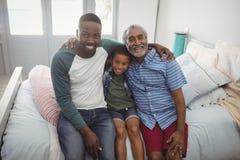 Famille sur plusieurs générations de sourire s'asseyant ensemble sur le lit Photographie stock