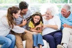 Famille sur plusieurs générations de sourire s'asseyant sur le sofa Photos libres de droits