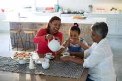 Famille sur plusieurs générations heureuse ayant le thé dans la table de salle à manger Photo libre de droits