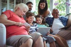 Famille sur plusieurs générations heureuse utilisant l'ordinateur portable, le téléphone portable et le comprimé numérique Photo libre de droits