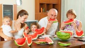 Famille sur plusieurs générations mangeant la pastèque Photos libres de droits