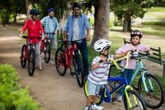 Famille sur plusieurs générations marchant avec la bicyclette en parc Photos libres de droits