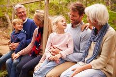 Famille sur plusieurs générations parlant sur un pont dans une forêt Image libre de droits