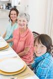 Famille sur plusieurs générations s'asseyant à la table de salle à manger Photographie stock libre de droits