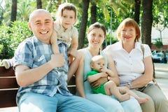 Famille sur plusieurs générations s'asseyant sur le banc en parc Photos stock