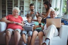 Famille sur plusieurs générations utilisant l'ordinateur portable, le téléphone portable et le comprimé numérique Photographie stock libre de droits