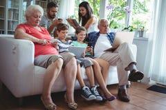 Famille sur plusieurs générations utilisant l'ordinateur portable, le téléphone portable et le comprimé numérique Photo libre de droits