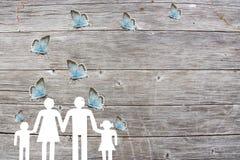 Famille sur un fond en bois avec le concept bleu d'assistance sociale de papillons Photos stock