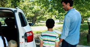 Famille sur un pique-nique enlevant le panier de la voiture banque de vidéos