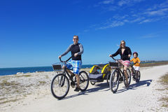 Famille sur un tour de bicyclette de plage ensemble Image stock