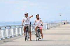 Famille sur un voyage faisant du vélo sur le bord de la mer Image stock